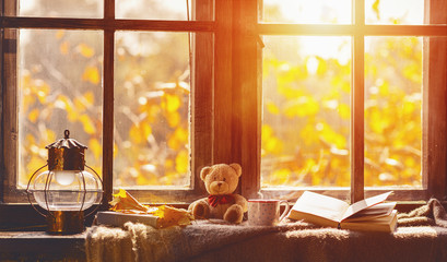 fall. cozy window with autumn leaves, book, mug of tea