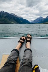 legs, feet and sandals on boat, Lake McDonald, Glacier National Park, Montana, Canada, United States of America , close up