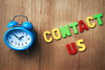 Wall Mural - clock and contact us word writen on wooden background