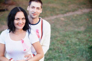 woman and man with pink ribbon for healing on world cancer day