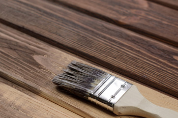 The process of painting wood surfaces with a brush. Unfinished p