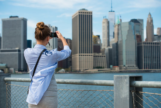 Tourist woman taking travel picture with camera of Manhattan Skyline and New York City skyline during autumn holidays. View from the back..
