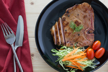 steak with salad and tomatoes on wood background