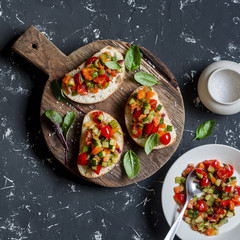 Photo sur Aluminium Singapoure Sandwiches with quick ratatouille on rustic cutting board on a dark background. Delicious healthy vegetarian food. Top view