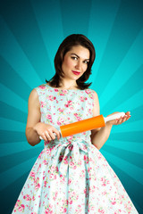Beauty smiling pin-up girl with rolling-pin.on blue background