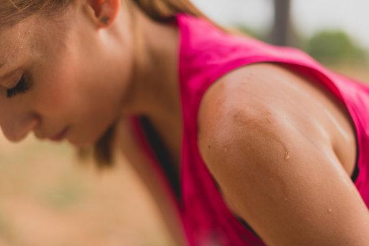 Sportswoman with sweaty skin after running