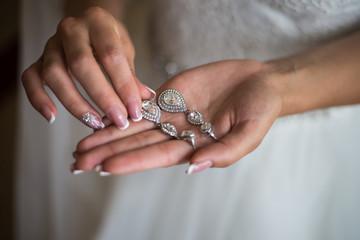 Wedding earrings on a female hand, she takes the earrings, the b