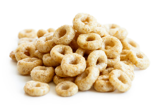 Heap of honey cheerios isolated on white.