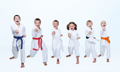 On a light background six karateka beating punch arm