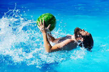 man with watermelon in swimming pool