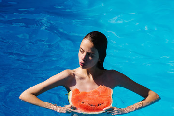 woman with watermelon in swimming pool