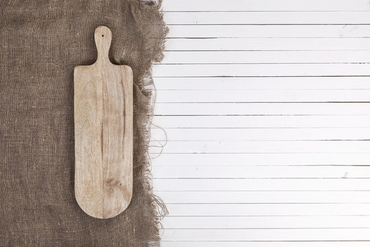 Empty cheeseboard on white wooden background, top view