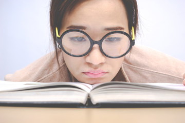 Nerdy young asian woman student with old big round glasses bored with reading book