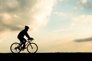 Silhouette of cyclist motion on sunset background