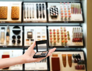 Female hand holding eyeshadow palette on blurred cosmetics shelf background. Beauty concept.