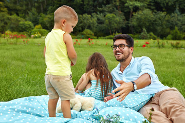 Father With Children Having Fun In Park. Happy Family In Nature