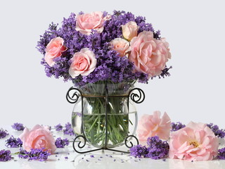 Bouquet of pink roses and lavender flowers in a vase. Romantic floral still life with bouquet of purple lavandula flowers and pink garden roses. Home decoration.