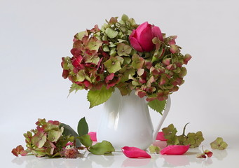 Autumn bouquet of hydrangea flowers and pink roses in a vase. Romantic floral still lfe with bouquet of fall hortensia flowers and roses in a vase and petals. Home decoration.
