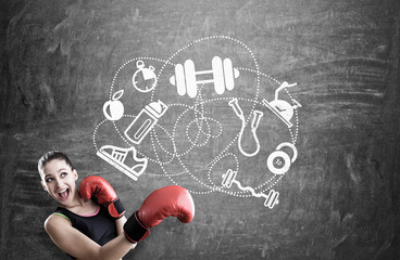 Woman boxer and sport icons on blackboard