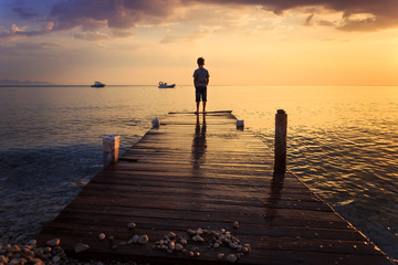 Child standing on a wooden pier at bright dramatic sunrise and looking at the sea