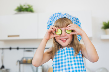 Funny little girl in cook clothes holds a slices of a cucumber on an eyes and puts out a tongue