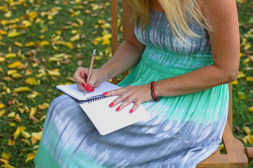 A blond woman wearing a summer dress and sitting on wooden chair in the garden. Female  writes a letter in a paper notebook. Autumn season with fallen leaves.