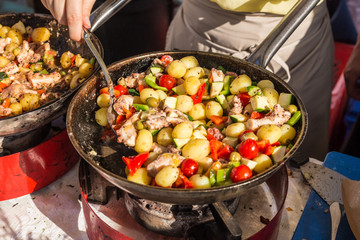 Cheff cooking traditional Mediterranean octopus with potatoes and vegetable on street stall on international street food festival of Odprta kuhna, Open kitchen event, in Ljubljana, Slovenia.