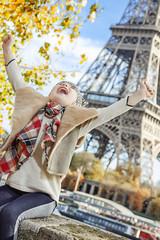 smiling elegant child on embankment in Paris, France rejoicing