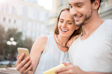Positive young couple using smart phone