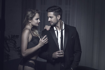 Rich macho young man drink whiskey with blonde lover
