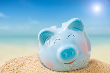 Summer happy piggy bank on sand beach over blurred tropical blue sea to saving vacation concept. blue sea background, Metaphor to saving concept.