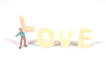 selective focus of miniature worker holding wood text love,abstract background to valentine concept.vintage tone.