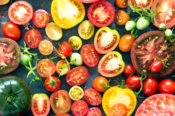 A lot of fresh and ripe tomatoes of different sizes and colours  – top view