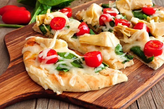 Healthy flat bread pizza with melted mozzarella, tomatoes, spinach and artichokes, close up on a paddle board