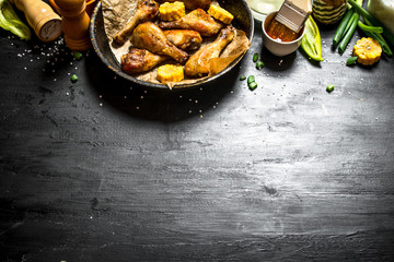 Fried chicken legs with pieces of corn and sauce.