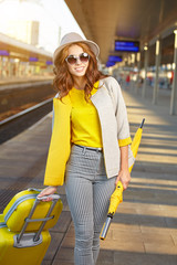 fair traveler with yellow suitcase at the station