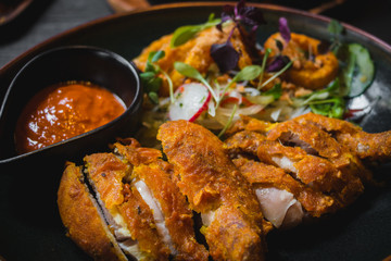 Fried Chicken with chili sauce and salad of radish, sprout, onio