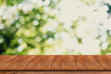 Wood table top on bokeh abstract green background - can be used