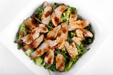 Sliced roasted fried pork with salad on white plate