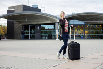 Woman With Wheeled Luggage Standing Outside Railroad Station