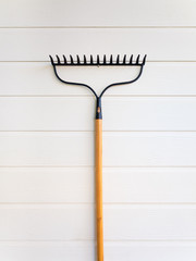 Rake hanging on white wooden texture wall