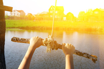 kids hands hold stick on swing rope