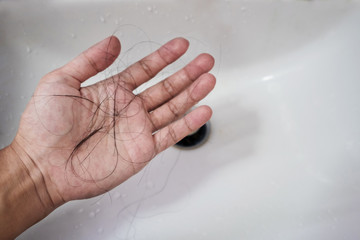 Close-up a man hand with loss hair, after taking shower, concepts of loosing hair