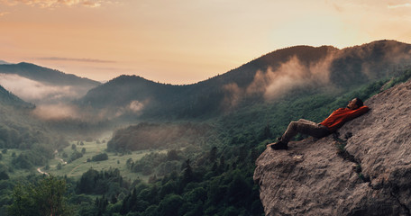 Traveler resting on top of cliff