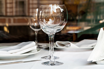 reflected in the empty glasses in a restaurant close up