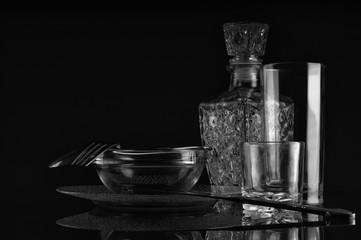 Glass tableware, glare on a dark background.
