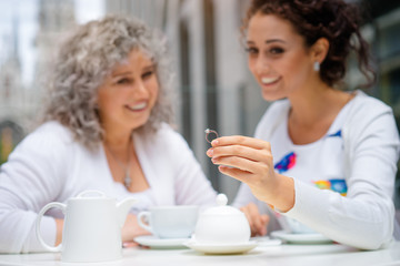 Pretty young woman showing engagement ring to her senior mother while they sitting at cafe.