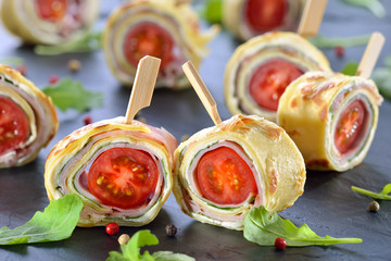 Leckere Crepes-Röllchen mit Schinken, Käse, Rucola und Tomate - Delicious finger food: Rolls of thin pancakes (crepes) with ham, cream cheese, rocket salad and cherry tomatoes