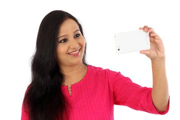 Happy young woman taking a selfie against white background
