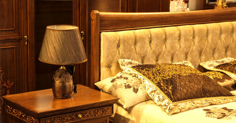 table lamp standing near the bed in the bedroom , on the bed pillows are beautiful